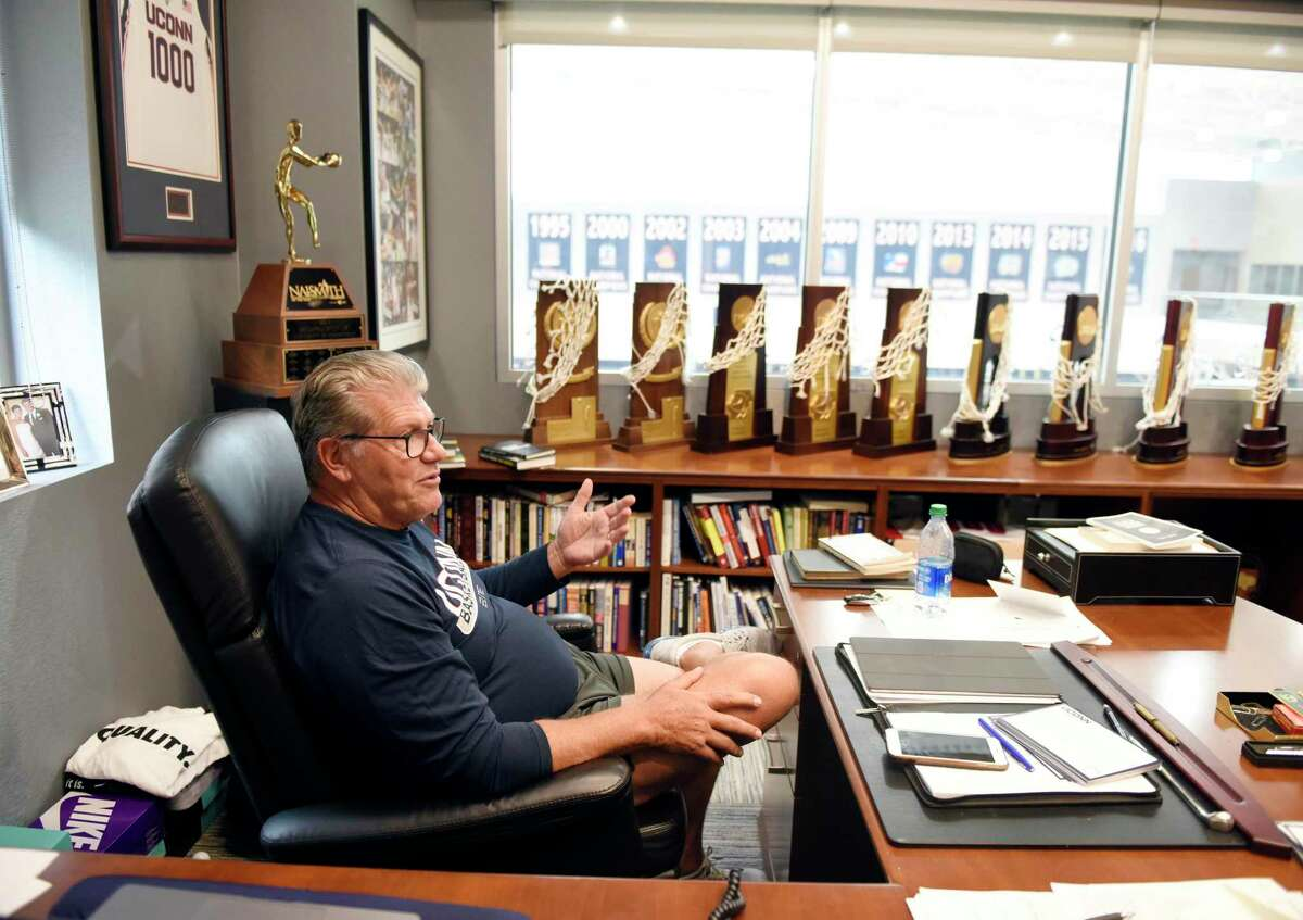 UConn women's basketball coach Geno Auriemma chats with his 11 national championship trophies displayed in his office at the Werth Family UConn Basketball Champions Center on the UConn main campus in Storrs, Conn. Monday, June 14, 2021.