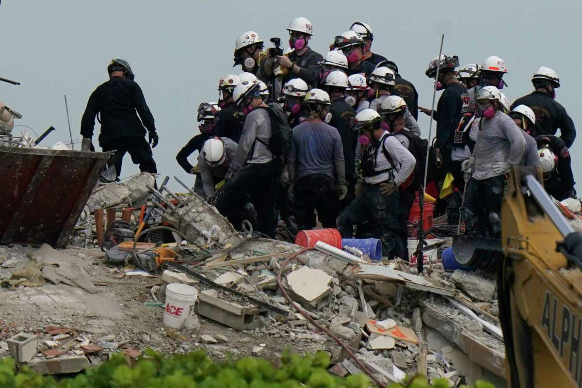 Search and rescue personnel work atop the rubble at the Champlain Towers South condo building, where scores of people remain missing almost a week after it partially collapsed, Wednesday, June 30, 2021, in Surfside, Fla.