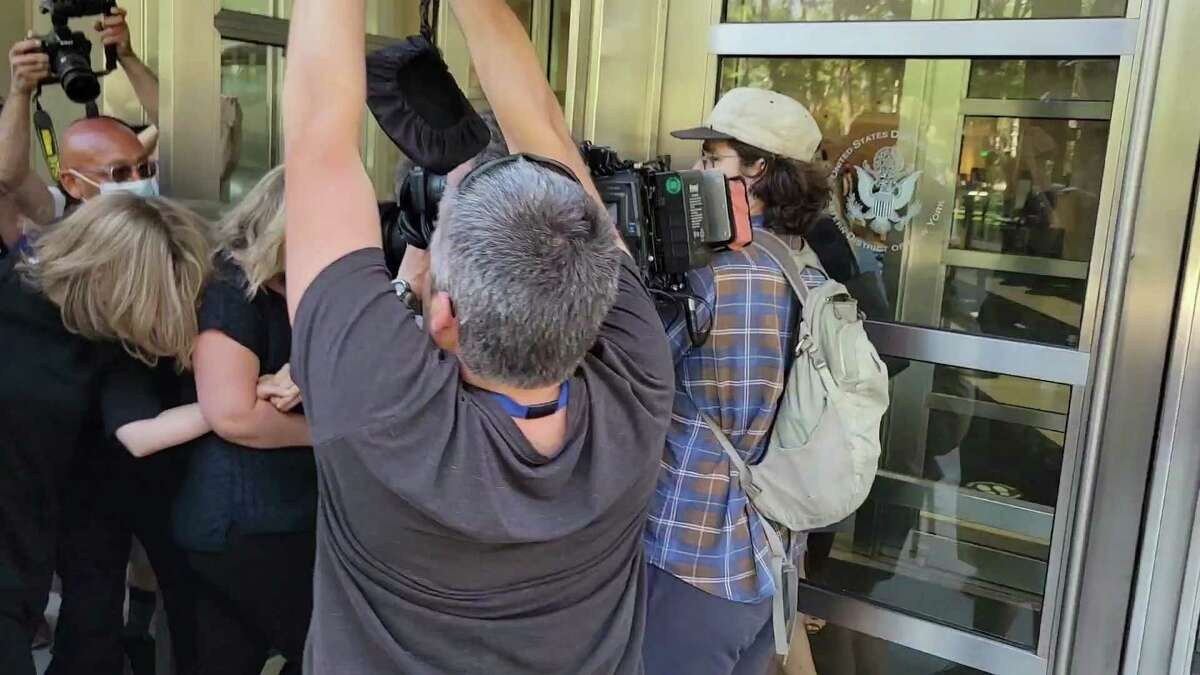 TV actress Allison Mack, left, crouches away from photographers as she arrives at Brooklyn Federal Court on Wednesday, June 30, 2021, in New York, for sentencing for her role in NXIVM.