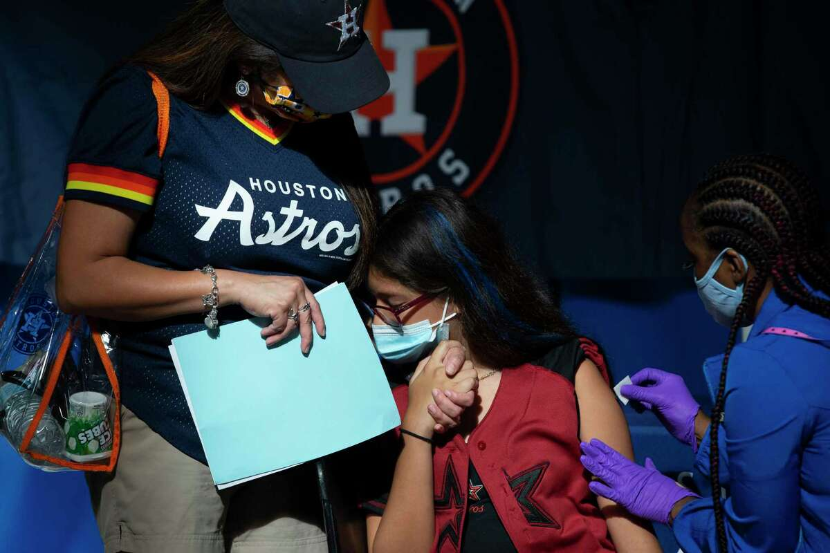 Trinity Garay, 12, hides into her mother Leticia Garay's arms while receiving her first does of COVID-19 vaccine, administered by Houston Methodist Medical Assistant Nyeshia Arceneaux, at the Astros' vaccination event Tuesday, June 29, 2021, at Minute Maid Park in Houston. Trinity said she was scared of the shot but it turned out to be OK. The Astros, in partnership with Houston Methodist, hosted free COVID-19 vaccinations to the public on Tuesday.