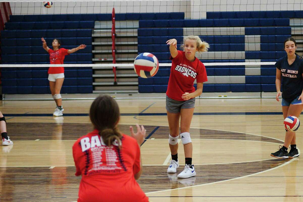 Gracie Rambin and Emma Iles participate in a serving drill Tuesday at the Bay Area Christian summer volleyball camp.