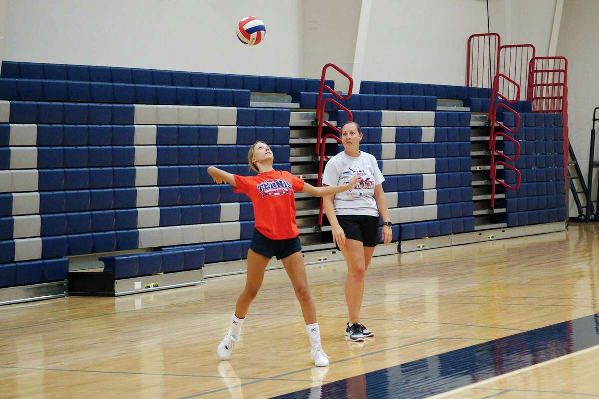 Bay Area Christian volleyball coach Christine Garner observes as Anya Fuller practices her serve during a drill at the BAC summer volleyball camp.