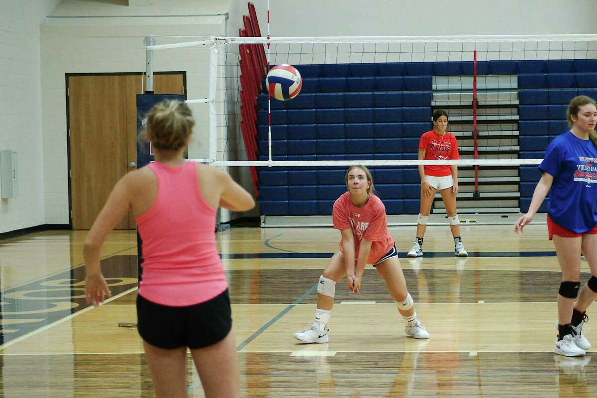 Claire Murphy and Anna Sewell participate in a setting drill at the Bay Area Christian summer volleyball camp.