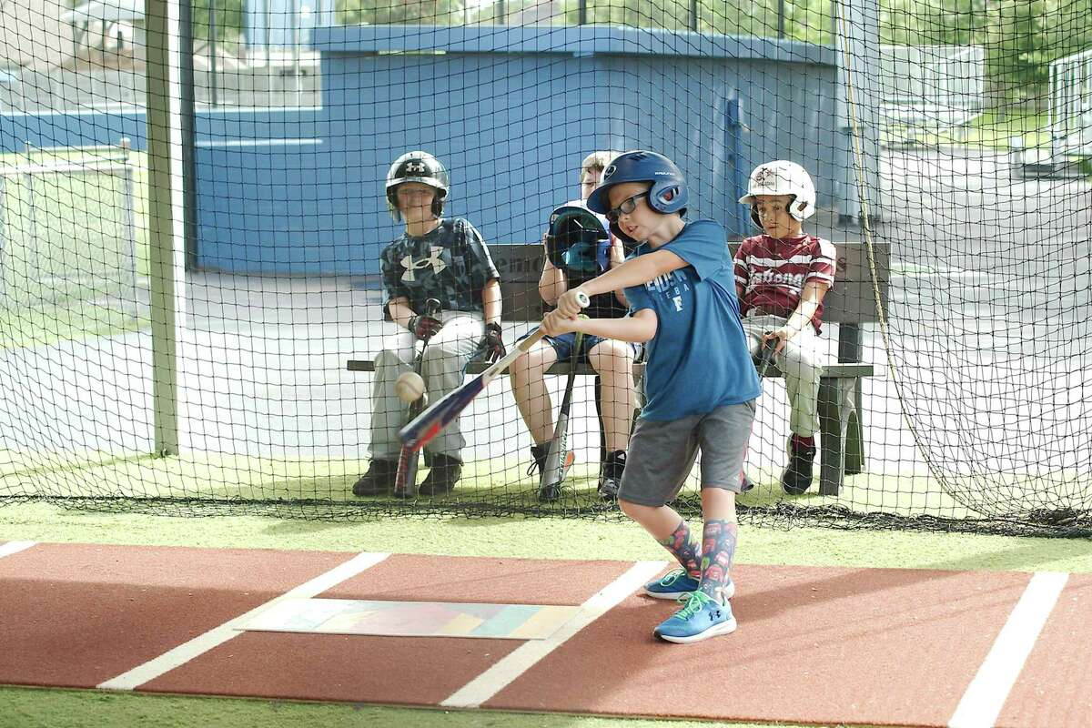 Riley Hanks practices his batting in the cages Tuesday at the Bay Area Christian baseball camp.