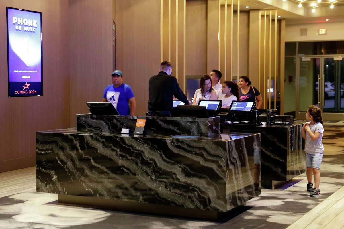 Customers and employees at the lobby ticket counter at the recently opened Star Cinema Grill multiplex movie theater Friday, Jun. 25, 2021 in Spring, TX.