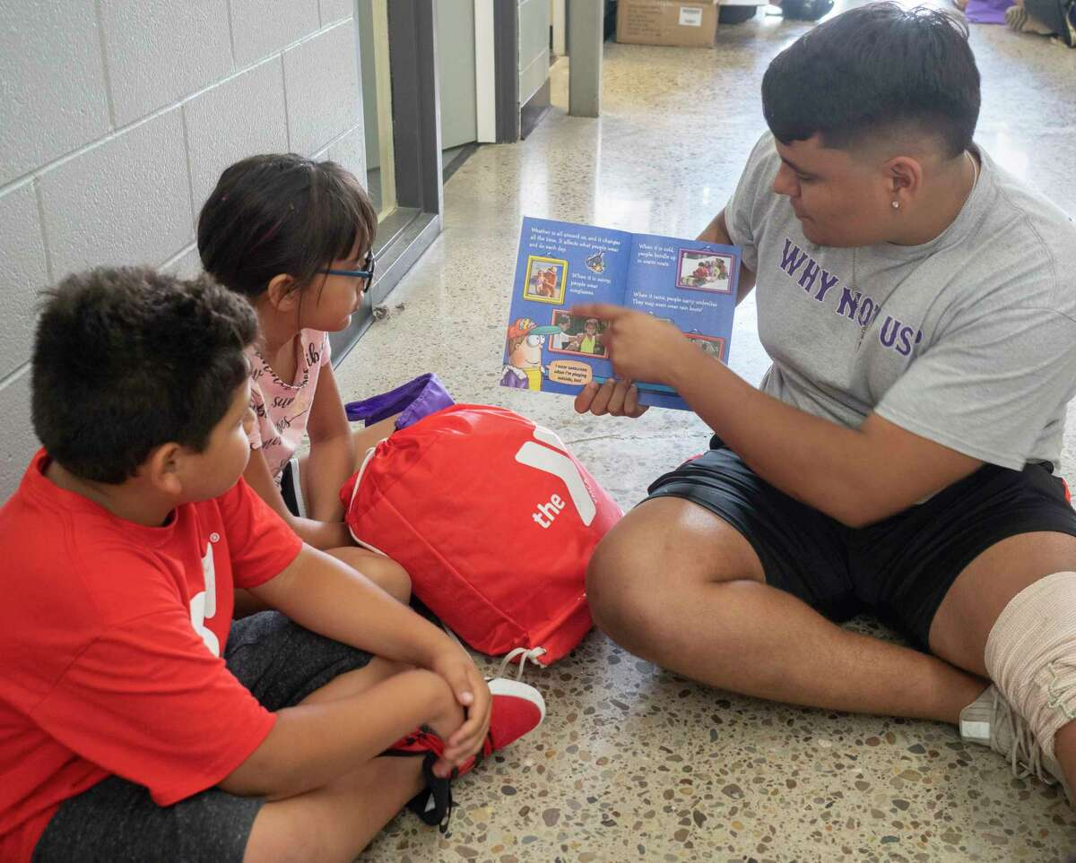 Midland High junior and senior football players read with children 06/30/2021 at the Midland YMCA. Diamondback Energy partnered with the MHS football program to provide the YMCA campers with a new backpack and four new books to take home, as well as a pizza lunch. Tim Fischer/Reporter-Telegram
