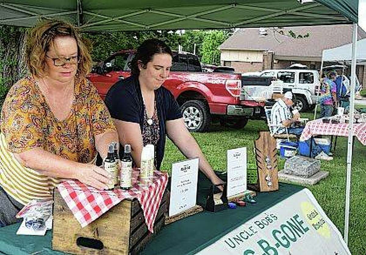 Kathy Hartley (left) and Meredith Kunz set up a booth Tuesday at the Bluffs Market. The market takes place from 4 to 6 p.m. Tuesdays on the city's downtown square. It features fresh foods, floral arrangements and other products. Some evenings include free live entertainment.