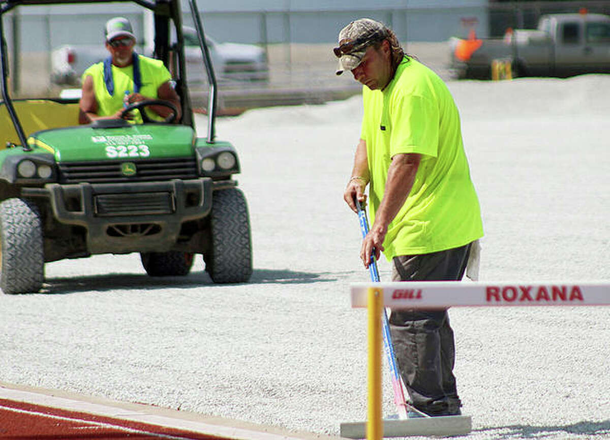 A worker from Byrne & Jones Construction of Bridgeton, Missouri evens out rock near the edge of Charles Raich field at Roxana High as part preparation for the installation of a new artificial turf playing surface.
