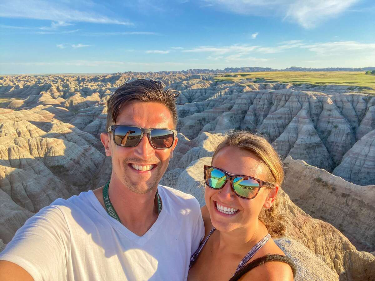 Alex Toombs (right) and her boyfriend Sam left their Bridgeport, Conn. life behind to move to Victoria Island, British Columbia and travel in a van to do so. They are pictured in Badlands National park in South Dakota.