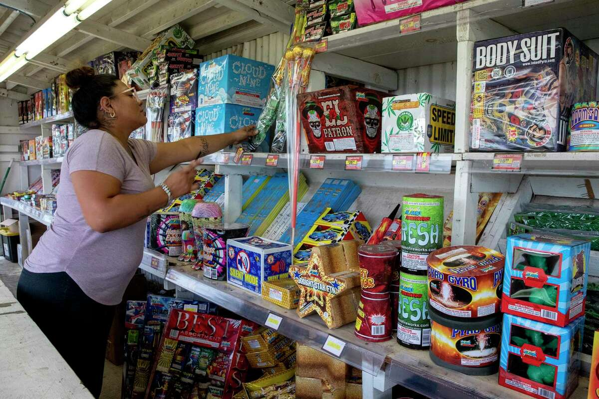 Neiva Garcia goes through her inventory of fireworks at the Alamo Fireworks stand she operates with her cousin, Crystal Casanova, on Walzem Road.