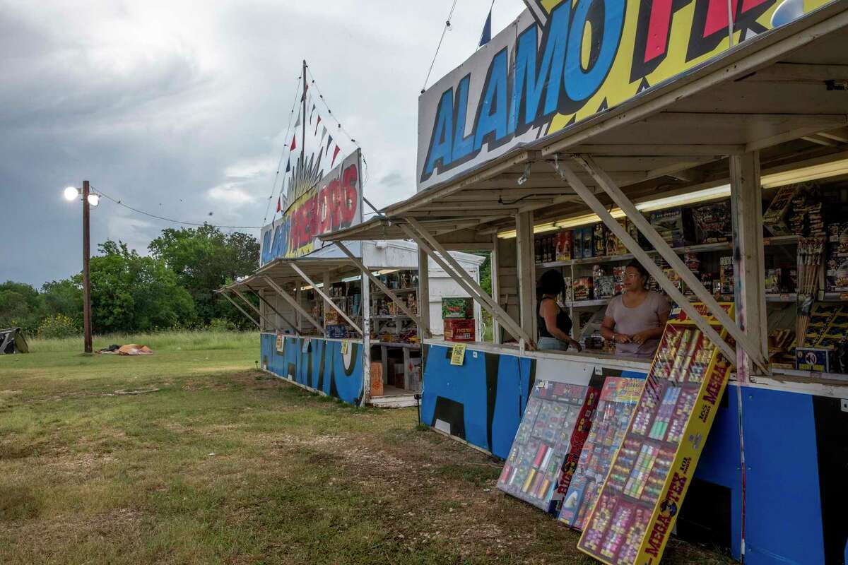 Cousins Crystal Casanova and Neiva Garcia sell fireworks at an Alamo Fireworks stand on Walzem Road.