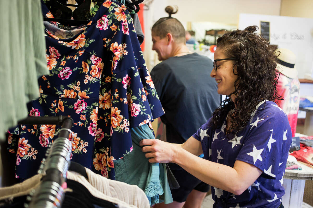 Sassy & Chic Boutique owner Angela Griffin, right, chats with customer Amy Tarvis of Midland, center, during the new store's grand opening Wednesday, June 30, 2021 at 4987 Eastman Ave. (Katy Kildee/kkildee@mdn.net)