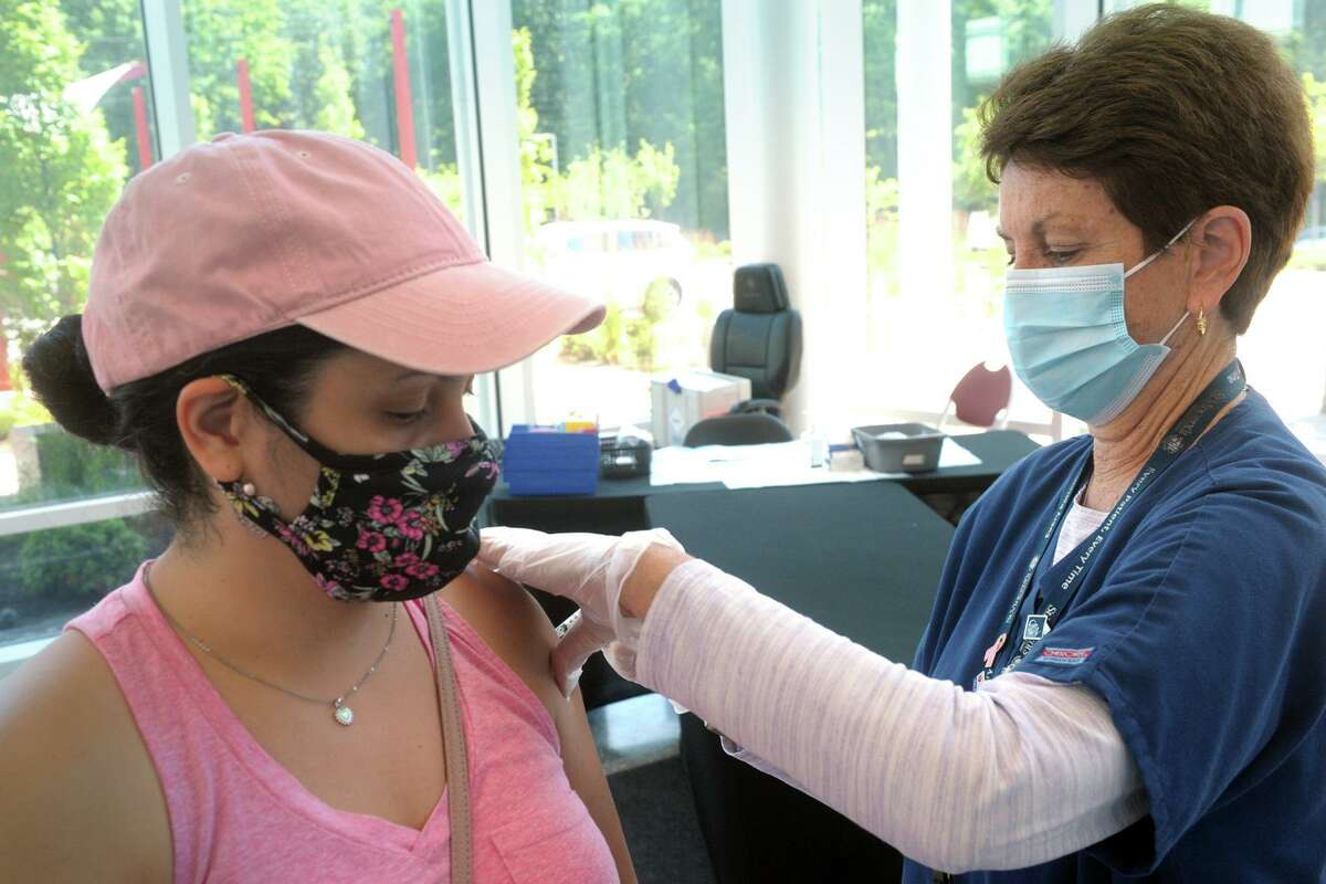 Wilza Cordero, of Ansonia, receives her second COVID-19 vaccination shot from St. Vincent's Medical Center nurse Mo Blees at the mass vaccination clinic on Sacred Heart University's West Campus, in Fairfield, Conn. June 30, 2021. Wednesday was the final day of vaccination operations at the Fairfield location.