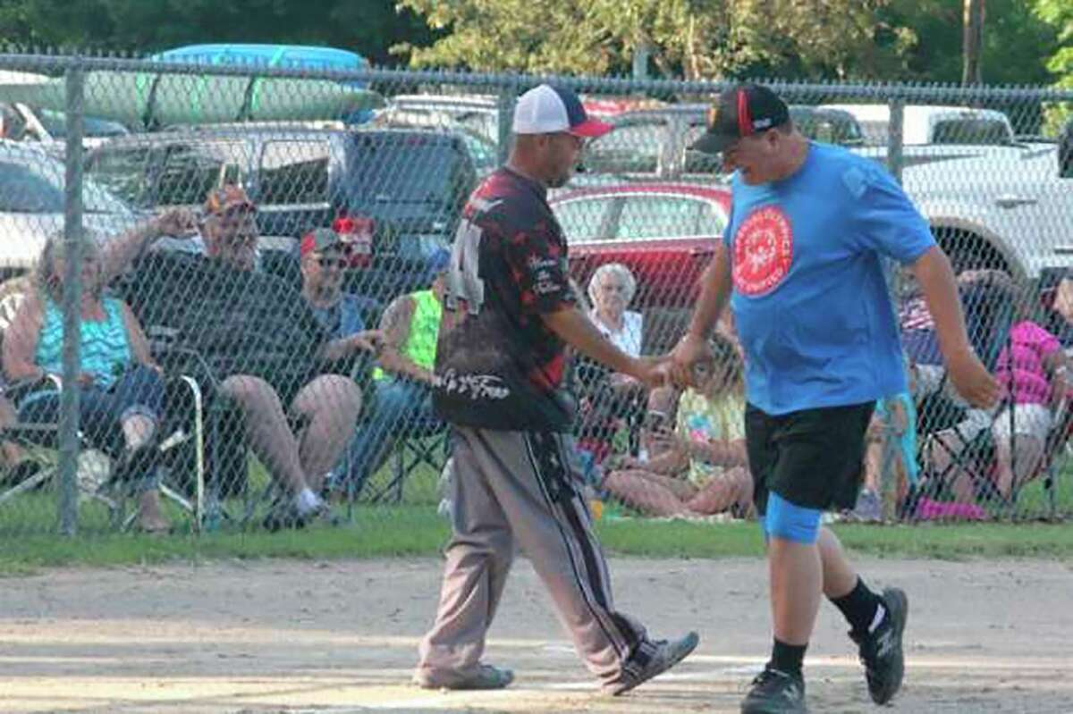 Old Timer Rob Young, right, is congratulated by Jim Haywood after belting a home run in theOld Timer's softball gamein 2019. (Pioneer file photo/John Raffel)