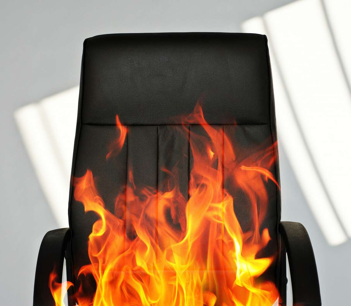 Conceptual photo of a black office chair on fire.