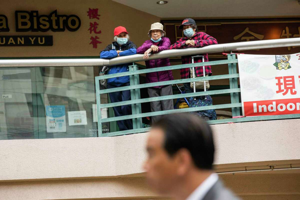 Three people watch from a balcony at Pacific Renaissance Plaza in Oakland's Chinatown as state Attorney General Rob Bonta speaks.
