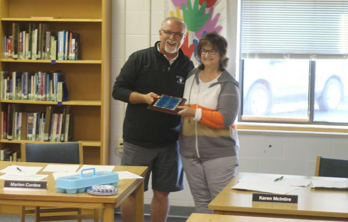 Marlen Cordes receives a plaque commemorating his retirement from Kaleva Norman Dickson school board president Karen McIntire.
