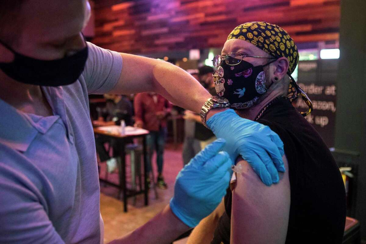Ian Speirer receives a dose of Moderna COVID-19 vaccine from Ruston Taylor during a pop-up vaccination clinic at BUDDY'S Houston in Montrose on Thursday, April 29, 2021 in Houston. BUDDY'S teamed up with Wellness Bar by Legacy to offer vaccines by appointment.