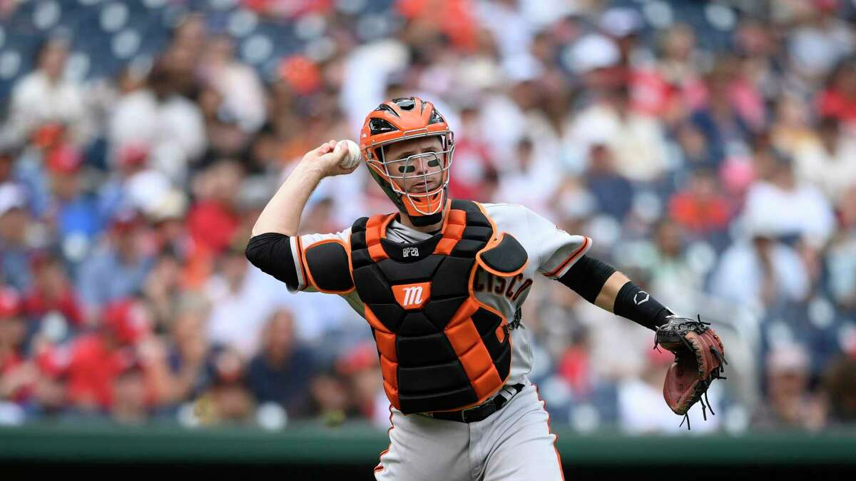 San Francisco Giants catcher Buster Posey throws to first to get out Washington Nationals' Joe Ross during the fourth inning of a baseball game, Sunday, June 13, 2021, in Washington. (AP Photo/Nick Wass)