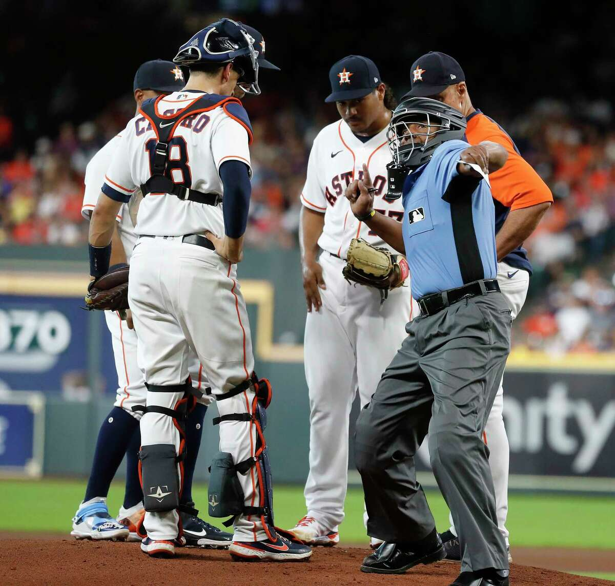 Home plate umpire CB Bucknor ejects Astros pitching coach Brent Strom (right) during a mound visit with starting pitcher Luis Garcia during the first inning Wednesday at Minute Maid Park.