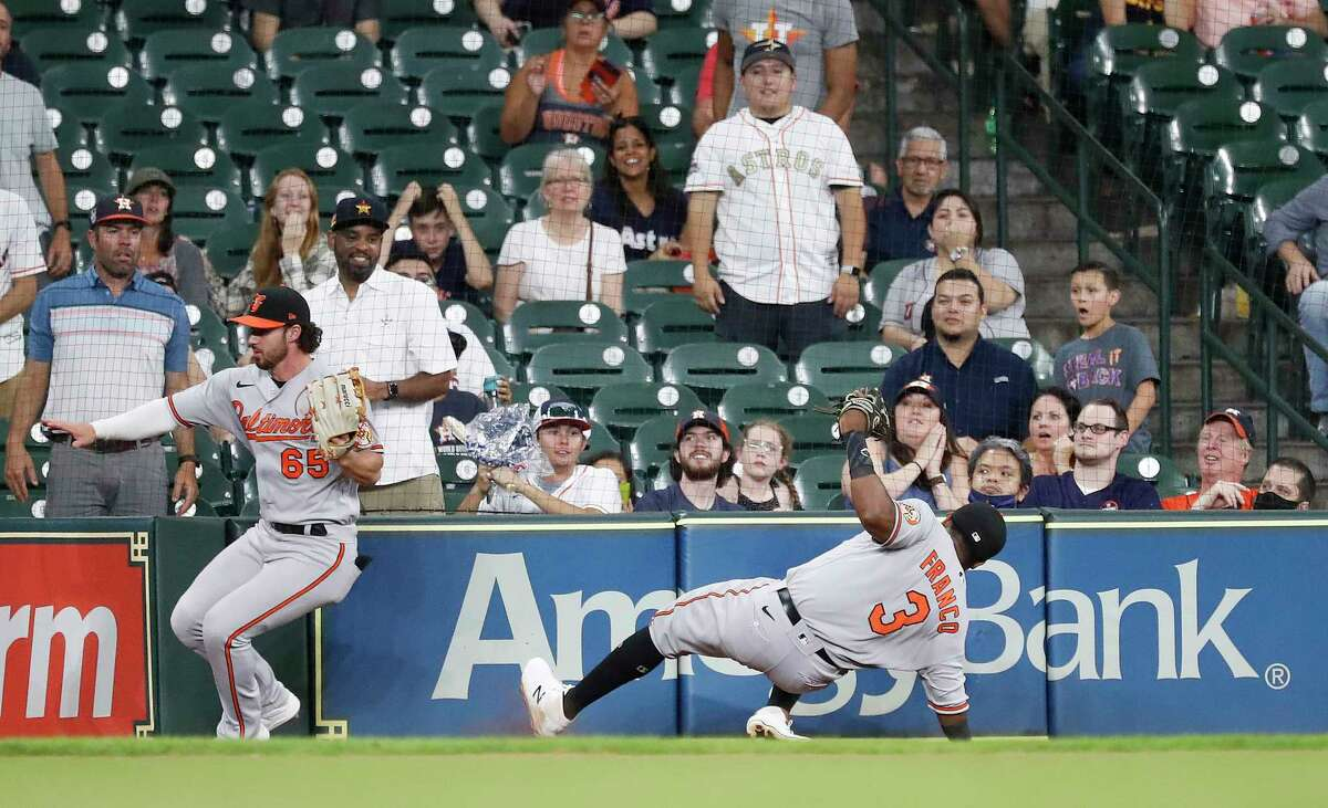 Baltimore Orioles third baseman Maikel Franco (3) slips and turns his ankle as he and Ryan McKenna (65) chased Houston Astros Robel Garcia's fly out to end an MLB baseball game at Minute Maid Park, Wednesday, June 30, 2021, in Houston. Astros lost 5-2 to the Baltimore Orioles.