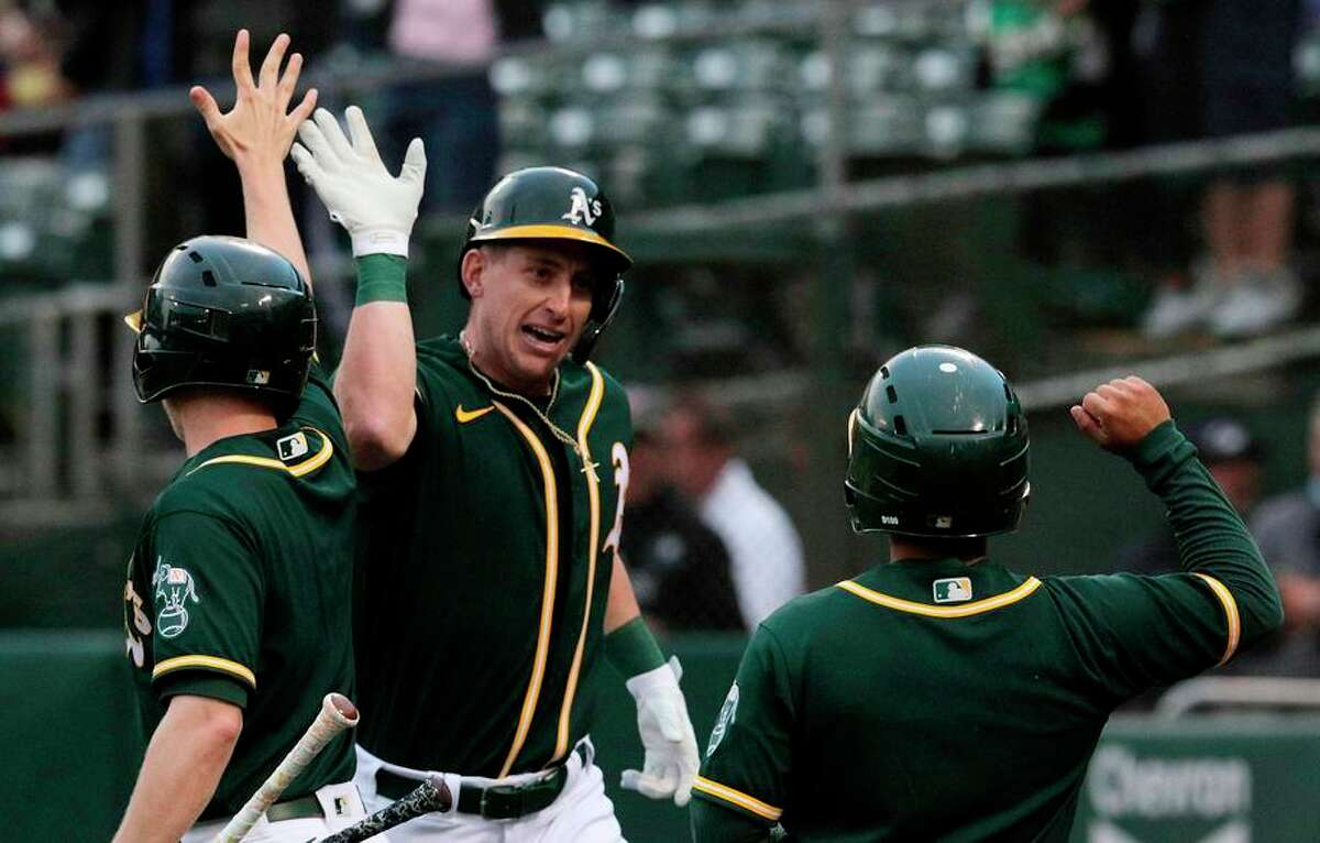 Frank Schwindel high-fives teammates after hitting a solo home run in the second inning at the Coliseum.