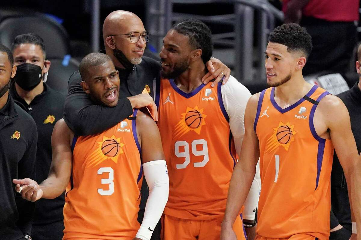 Phoenix Suns head coach Monty Williams, second from left, hugs Chris Paul, left, and Jae Crowder, second from right, as Devin Booker stands by as time runs out in Game 6 of the NBA basketball Western Conference Finals against the Los Angeles Clippers Wednesday, June 30, 2021, in Los Angeles. The Suns won the game 130-103 to take the series 4-2. (AP Photo/Mark J. Terrill)
