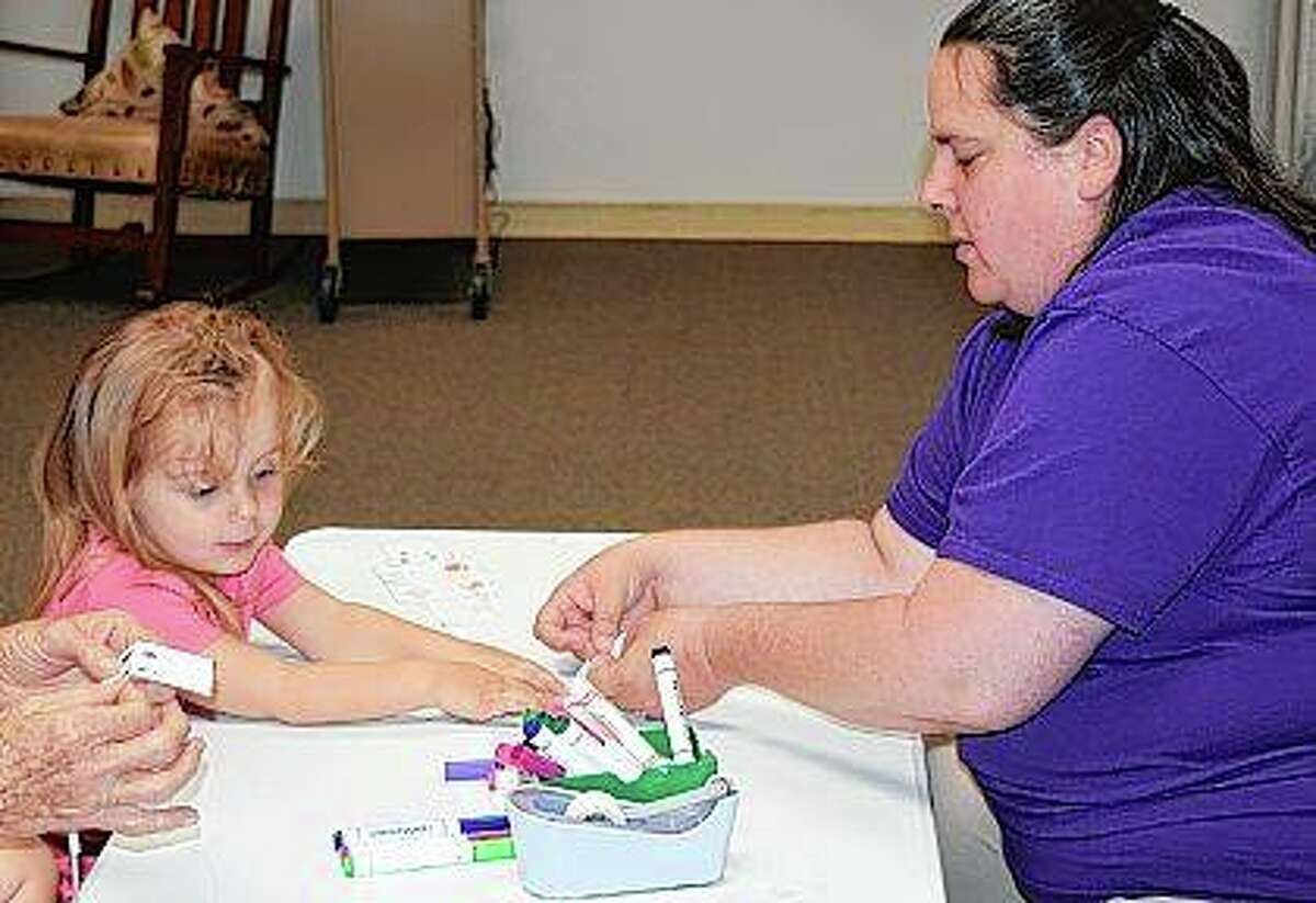 """Hazel Leak, 3, considers the colors of markers available Wednesday at Jacksonville Public Library while working on building a car robot with help from Cindy Boehlke, the library's youth services director. The library sponsored a science-themed activity after a storytime reading of """"Randy Riley's Really Big Hit."""""""