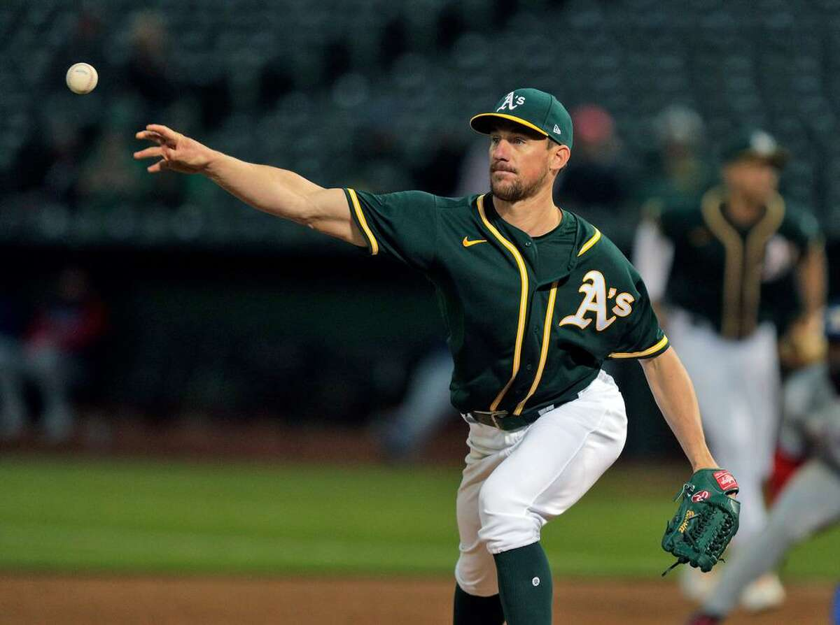 Chris Bassitt (40) throws to third on a pick attempt in the sixth inning as the Oakland Athletics played the Texas Rangers at the Coliseum in Oakland, Calif., on Wednesday, June 30, 2021.