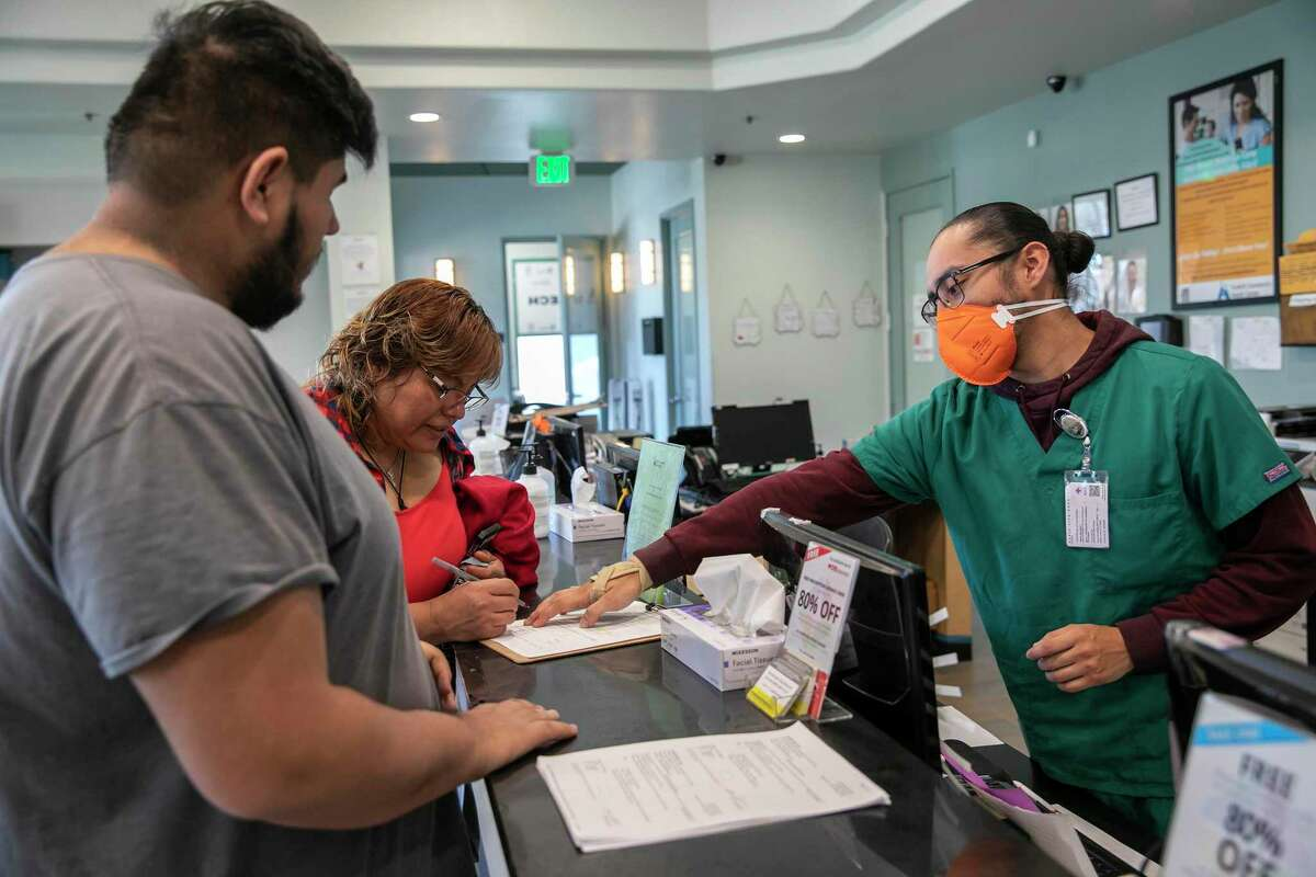 Wearing an N95 face mask, medical assistant Edwin Moreno (right) helps patients Jose Hernandez and Antonia Hernandez at the Foothill Community Health Center in San Jose.