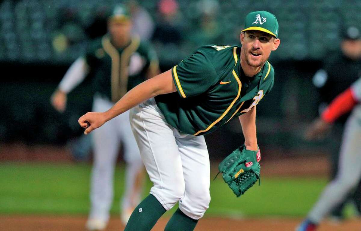 Chris Bassitt (40) watches his throw to third on a pick attempt in the sixth inning as the Oakland Athletics played the Texas Rangers at the Coliseum in Oakland, Calif., on Wednesday, June 30, 2021.