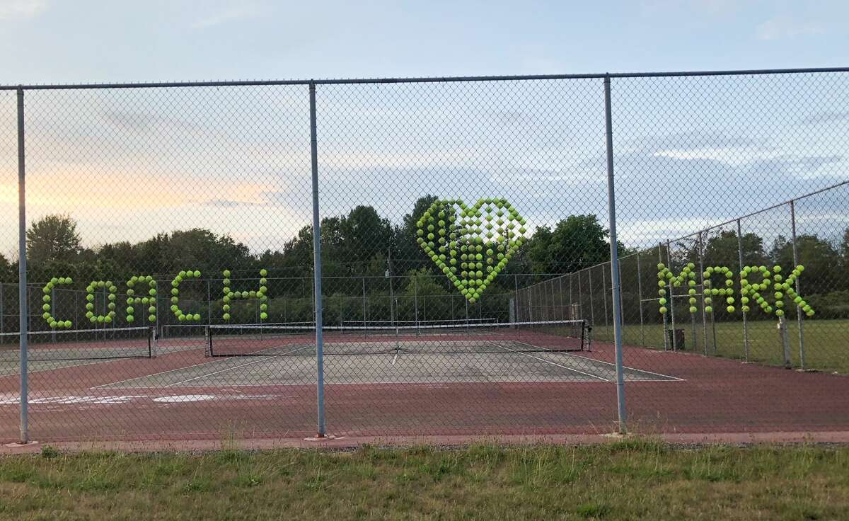 The members of the Bad Axe girls tennis team created a memorial for their coach, Mark Prescott, who died June 23 in a cycling accident.