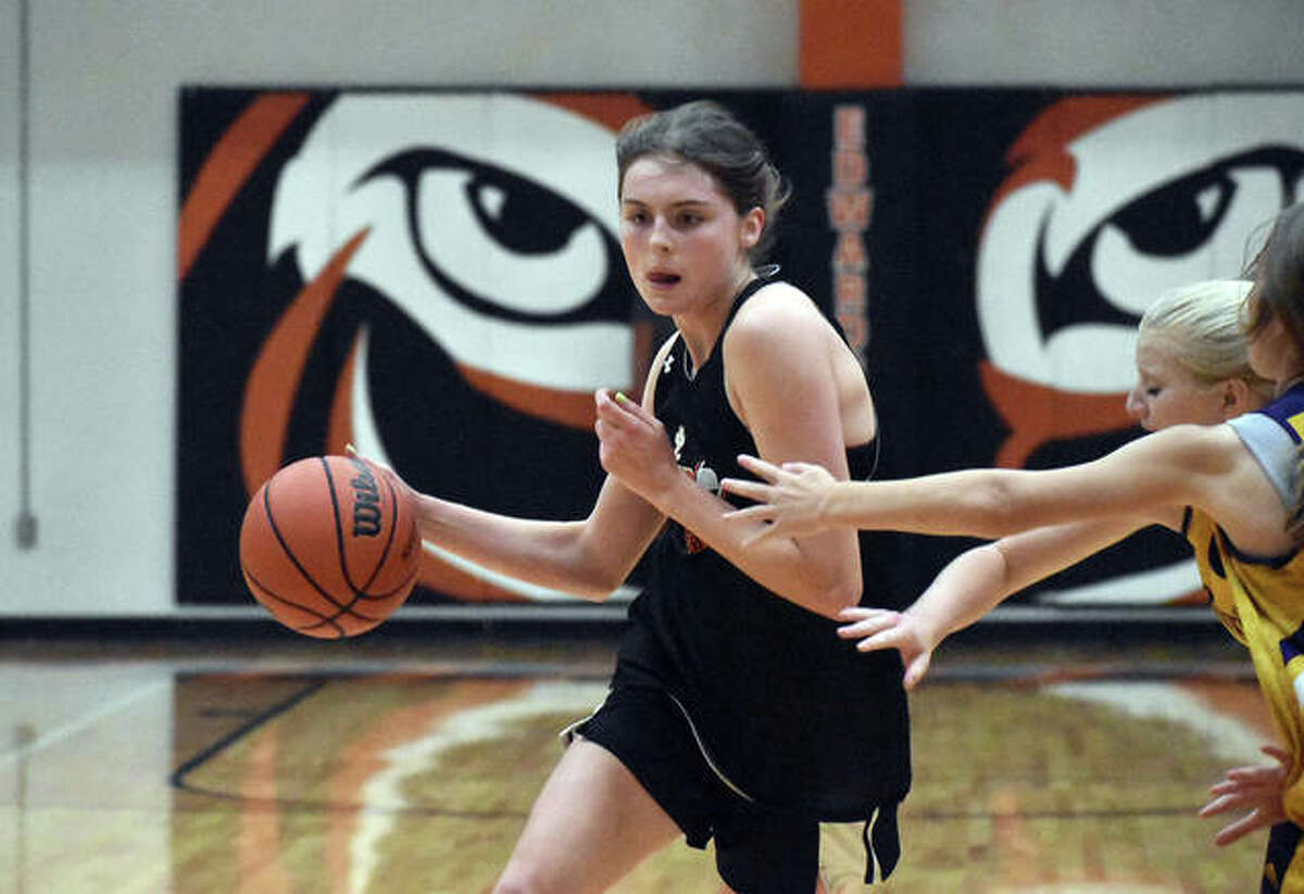 Edwardsville senior guard Elle Evans drives around a pair of Civic Memorial defenders during the EHS Shootout on Tuesday in Edwardsville.