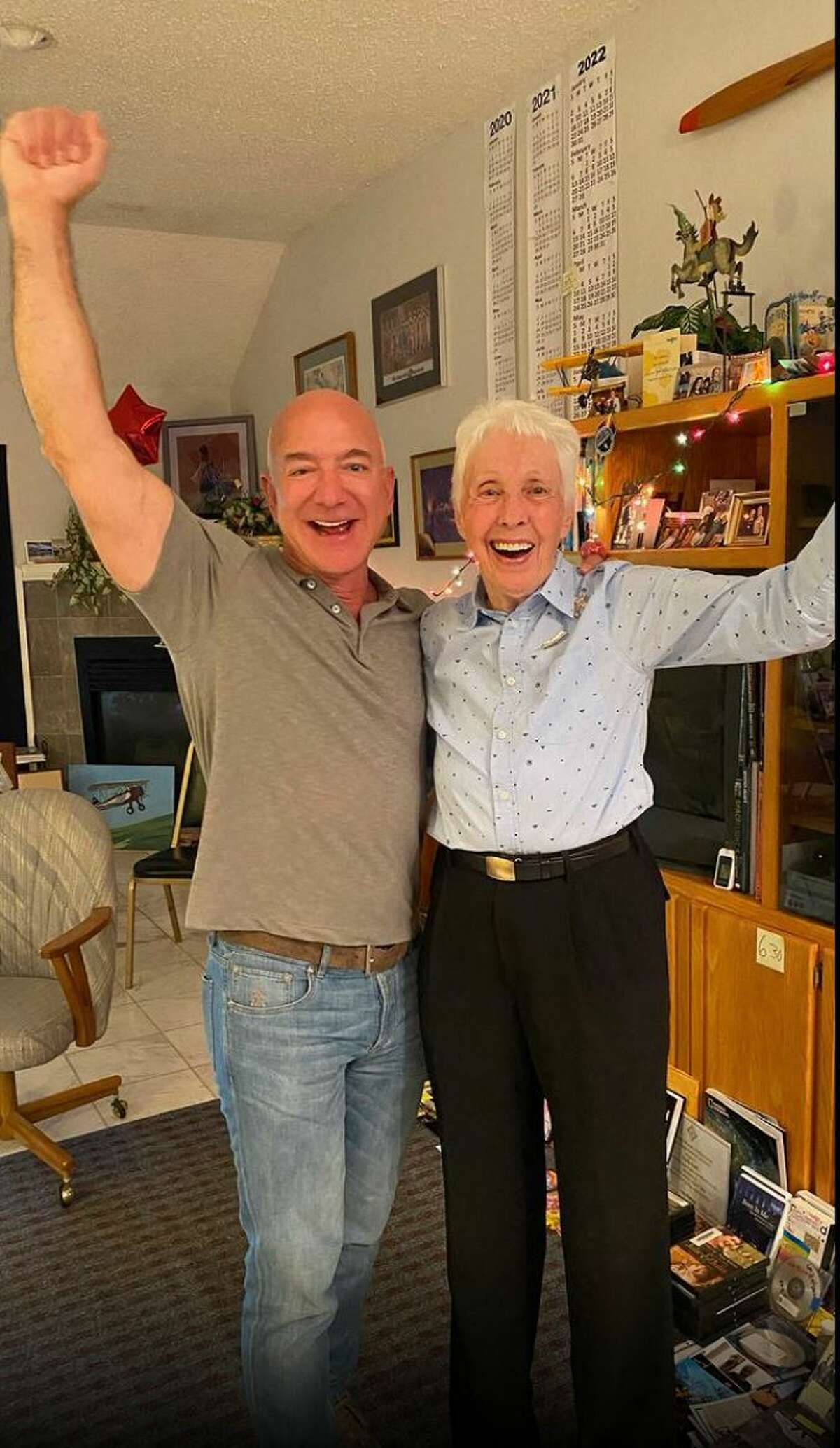 """This image posted on Jeff Bezos Instagram account (@jeffbezos) and on the Blue Origin website on July 1st, 2021 shows the moment when Amazon and Blue Origin founder Jeff Bezos (L) announces to Wally Funk (R) she will fly to Space with him on the Blue Origin's New Sheppard first human flight. - Wally Funk, a 82-year-old woman pilot, will join Jeff Bezos in traveling to space this month on the first crewed spaceflight for the billionaire's company Blue Origin, the firm announced Thursday. Funk will become the oldest person ever to fly to space when she takes part in the July 20 journey aboard the New Shepard launch vehicle along with Bezos, his brother Mark and the unnamed winner of an auction for another seat on the aircraft. (Photo by - / BLUE ORIGIN / AFP) / RESTRICTED TO EDITORIAL USE - MANDATORY CREDIT """"AFP PHOTO /BLUE ORIGIN"""" - NO MARKETING - NO ADVERTISING CAMPAIGNS - DISTRIBUTED AS A SERVICE TO CLIENTS"""