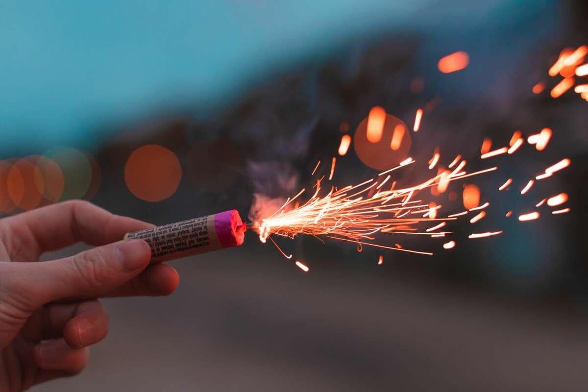 Hand holding a lit firework.
