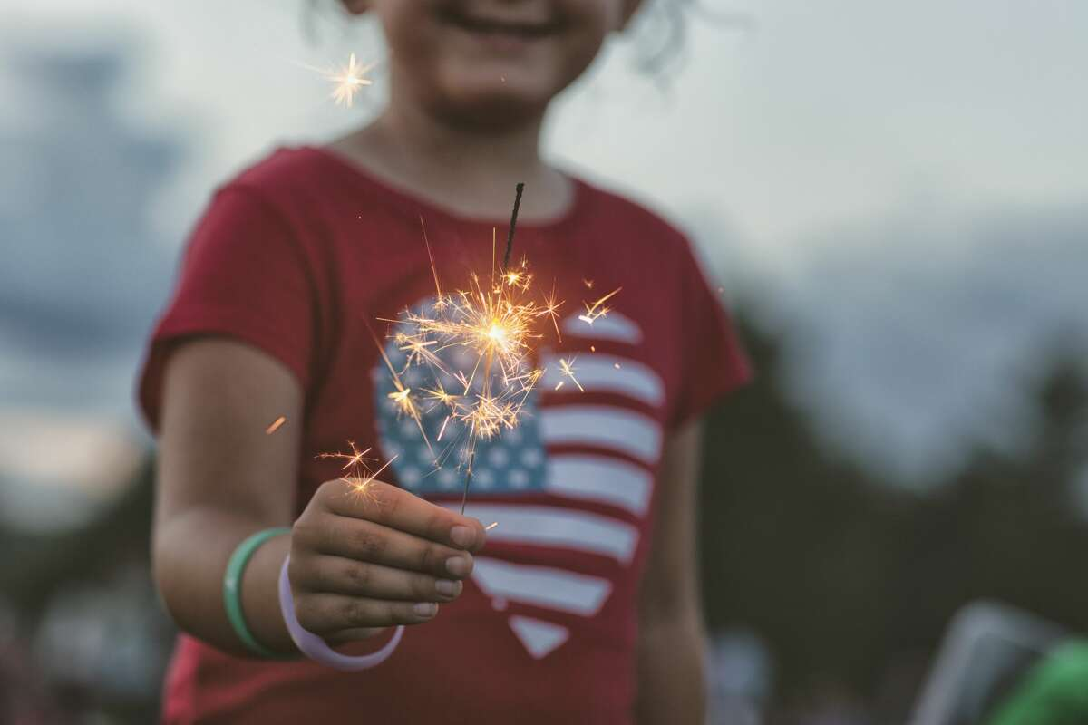 Young girl holding a lit sparkler.