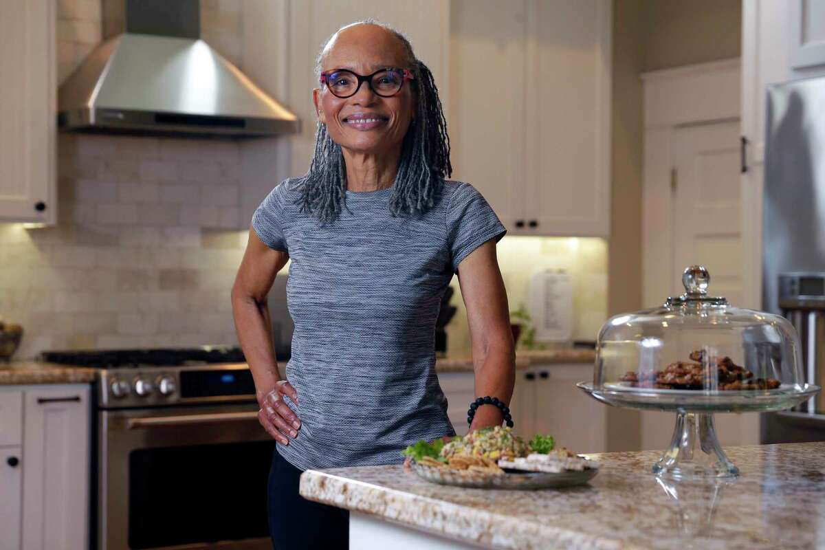 """Black vegan Sherra Aguirre in her home kitchen with vegan chocolate chip cookies and tuna salad, made from chick peas,Thursday, Jun. 24, 2021 in Houston, TX. Aquirre has written a new book to empower people of color to eat healthier, titled """"Joyful Delicious Vegan: Life Without Heart Disease."""""""