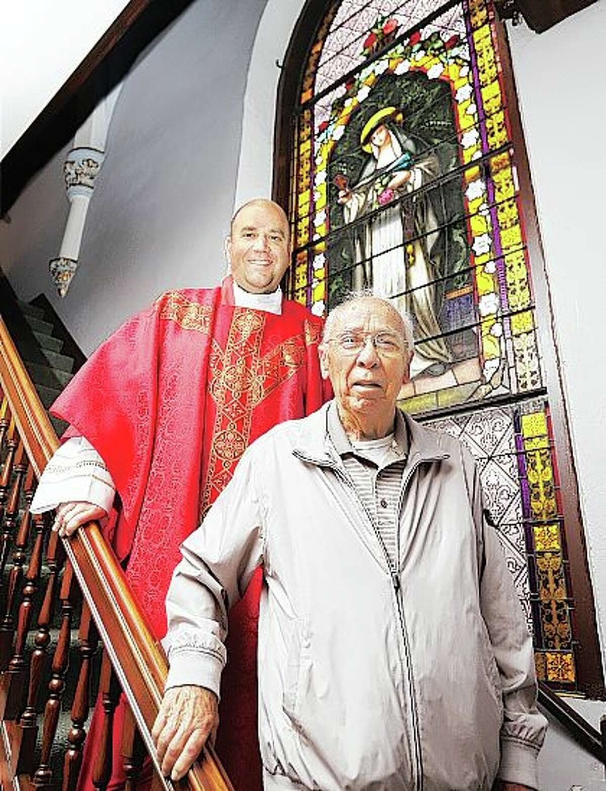 The Rev. Martin Smith stands with longtime St. Francis Xavier Church member John Thurston in front of one of the stained glass windows in the church. The church will celebrating its 150th anniversary with a Mass and reception Sunday.