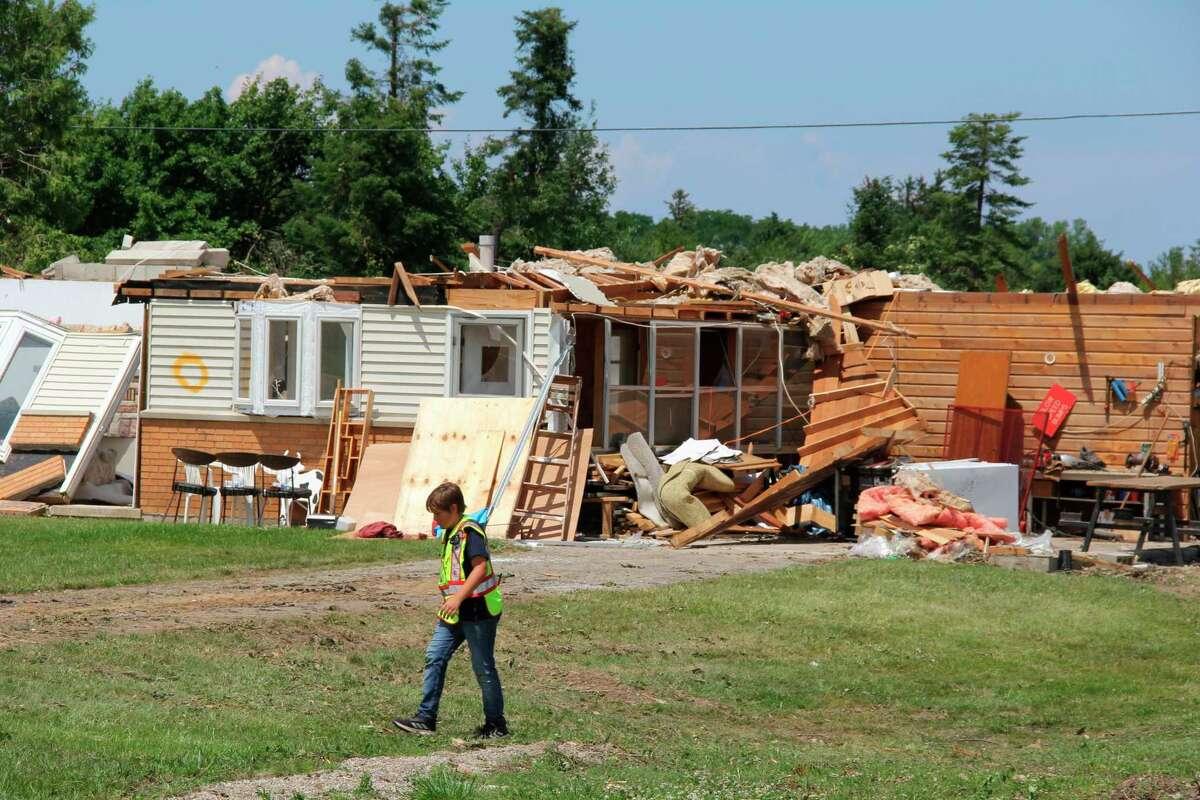 Volunteers help clean up the tornado damage on Grindstone Road in Port Austin on Wednesday. (Robert Creenan/Huron Daily Tribune)