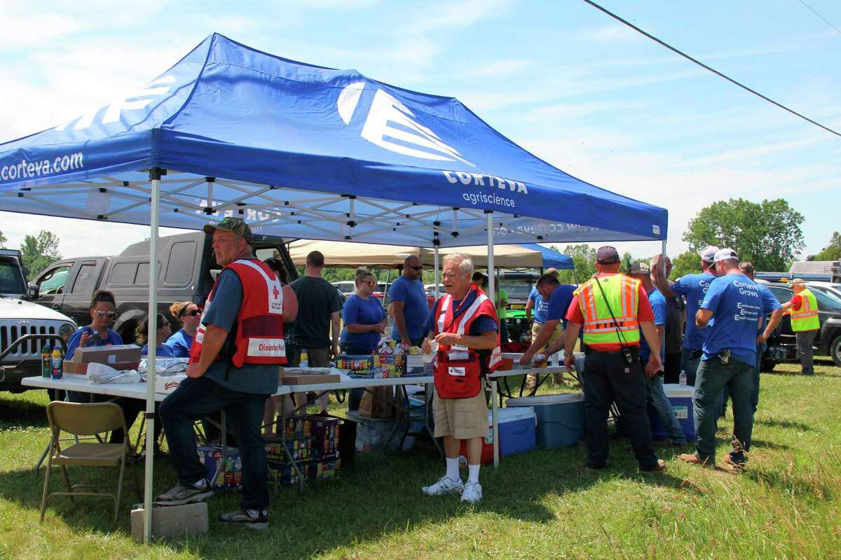 A tent set up by Corteva Agriscience employees gave out food and water to volunteers helping clean up the tornado damage in Port Austin on Wednesday. Organizers estimated around 300 people helped out total. (Robert Creenan/Huron Daily Tribune)