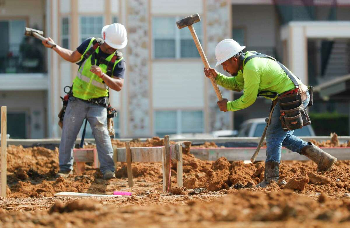 Construction workers use sledgehammers to drive wooden stakes for the perimeter of a building's foundation along Texas 105, Tuesday, June 15, 2021, in Montgomery.
