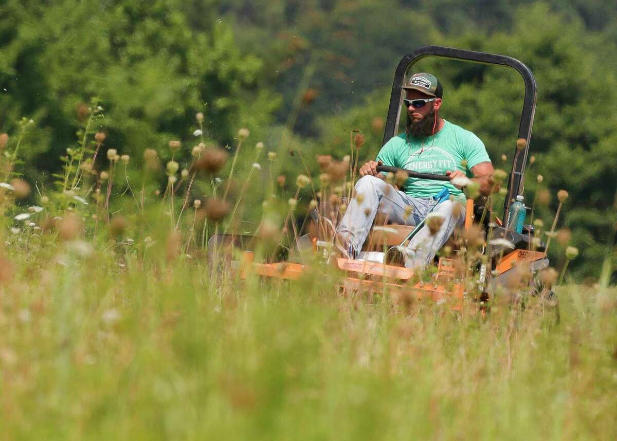 """David Tyner mows a field along Texas 105 for the city of Conroe, Tuesday, June 15, 2021. """"It's brutal,"""" Tyner said as temperatures at 10:30 a.m. already reached 94 degrees. """"June is just brutally hot, and July and August are even worst. But we're out here no matter what. It's something we take pride in making Conroe look good."""""""