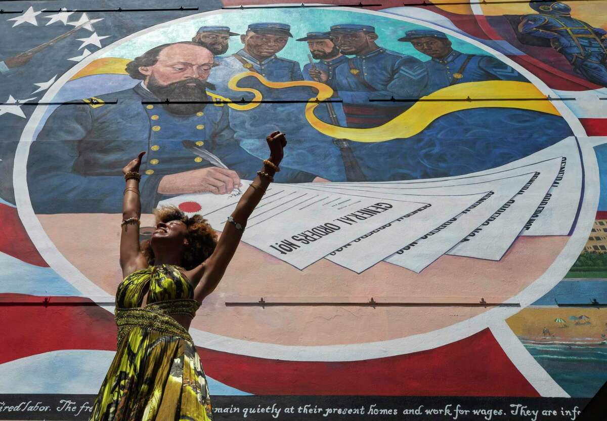"""Dancer Prescylia Mae, of Houston, performs during a dedication ceremony for the massive mural """"Absolute Equality"""" in downtown Galveston, Texas, Saturday, June 19, 2021. The dedication of the mural, which chronicles the history and legacy of Black people in the United States, was one of several Juneteenth celebrations across the city. (Stuart Villanueva/The Galveston County Daily News via AP)"""