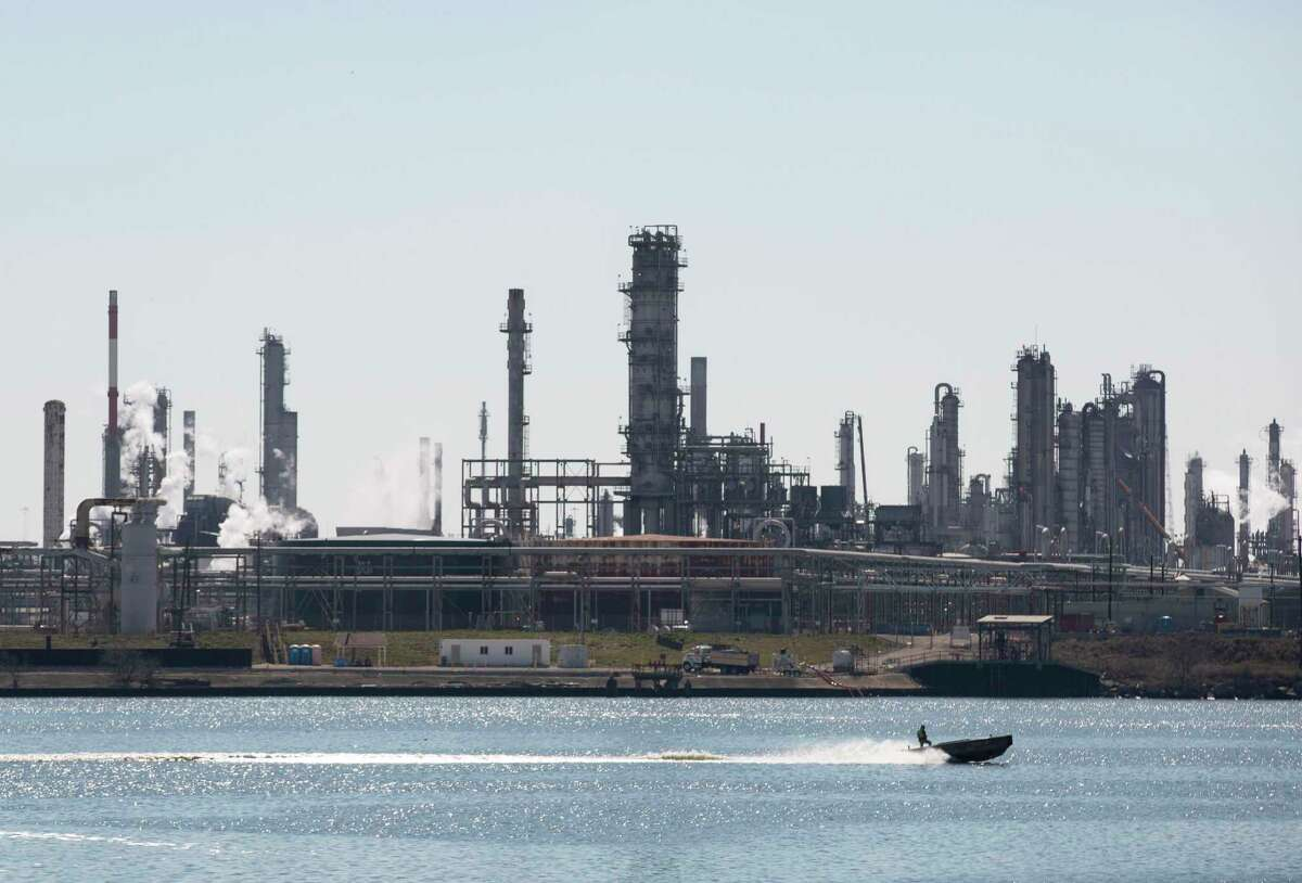 A small boat passes refineries in the background Tuesday, Feb. 2, 2021, in the Houston Ship Channel.