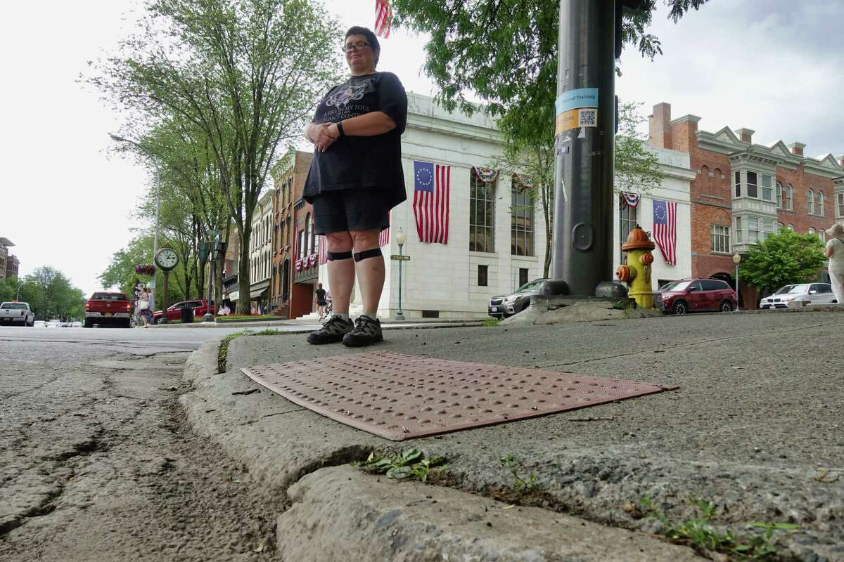 """Darlene McGraw stands on the sidewalk at the corner of Broadway and Lake Ave. on Thursday, July 1, 2021, in Saratoga Springs, N.Y. McGraw says that this area has major issues for people using a mobility device. """"The curb cut is not level with the road surface and the slope leading away from the road is too great"""", McGraw says. McGraw also says that she feels it is not ADA compliant. (Paul Buckowski/Times Union)"""