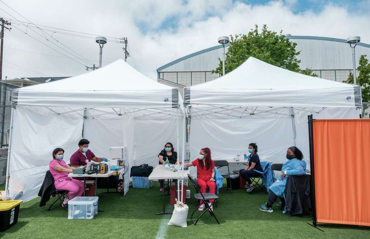 Support staff at the COVID-19 vaccination tent await participants as Carnaval celebrations kicked off in San Francisco in May, about two weeks before California lifted most of its pandemic restrictions in public life. Since the reopening, new coronavirus cases in California have increased more than 20%.