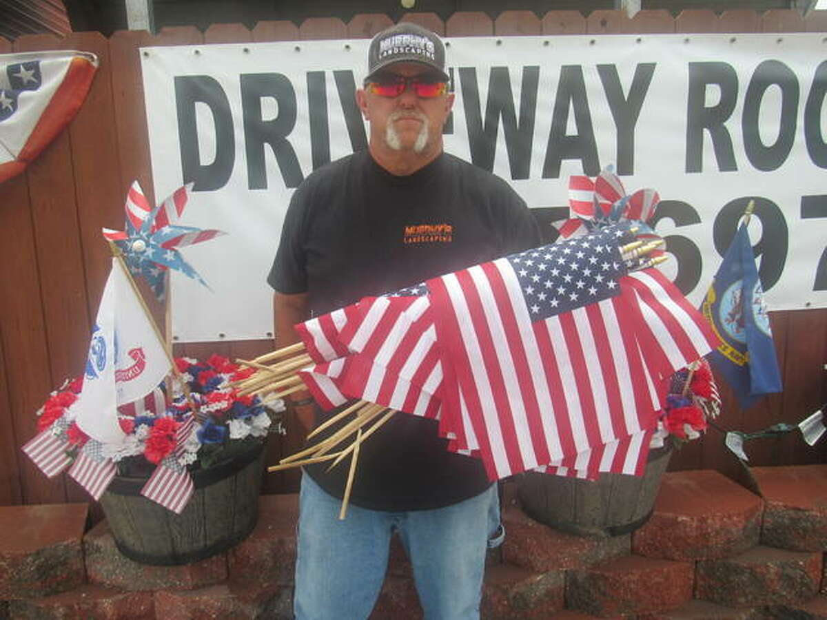 Jim Murphy holds some of flags knocked down Tuesday by an unknown motorist near his business in Cottage Hills. While some of the 250-300 flags were salvagable, Murphy said most were destroyed.