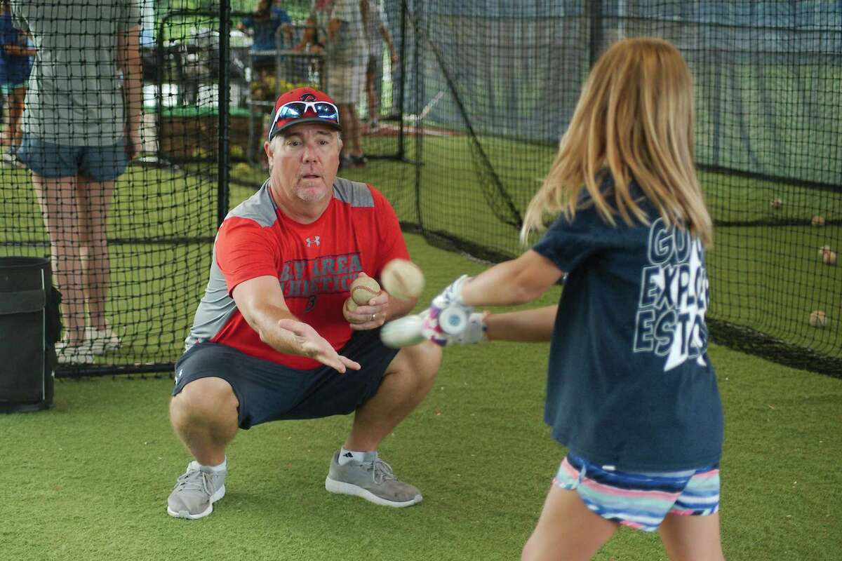 Bay Area Christian softball coach Jason Atwell assists Claire Sledge during a batting drill Wednesday at the BAC summer softball camp.