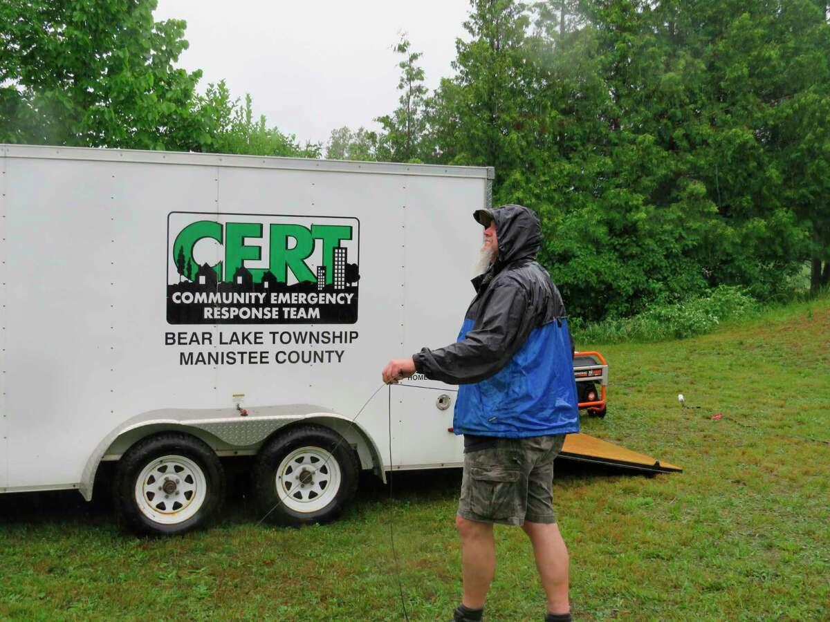 Carl Begley, a CERT coordinator, strings an antenna line in the rain recently. (Courtesy photo)