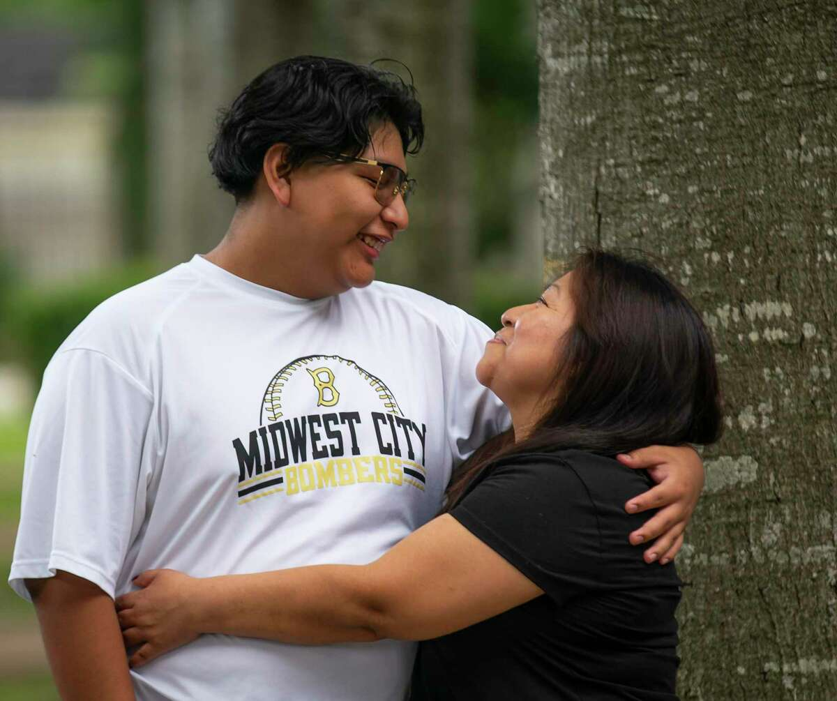 Graciela Lopez hugs her son Jose Mejia, 17, who will be a senior this fall at Elsik High School, outside of their home, Friday, June 25, 2021, in Houston. The family was recently surprised to discover that Jose had won a $5000 scholarship as part of a Harris County led incentive program towards vaccinating teenagers.